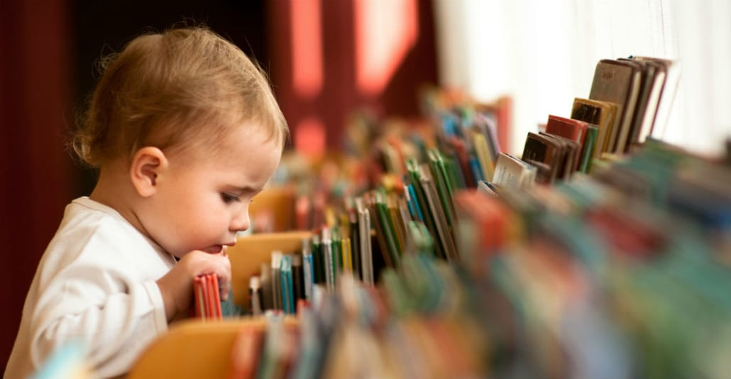 child looking at books and picking out a book