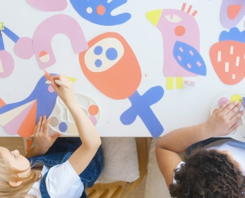 two kids making art with colored cut-outs on a table
