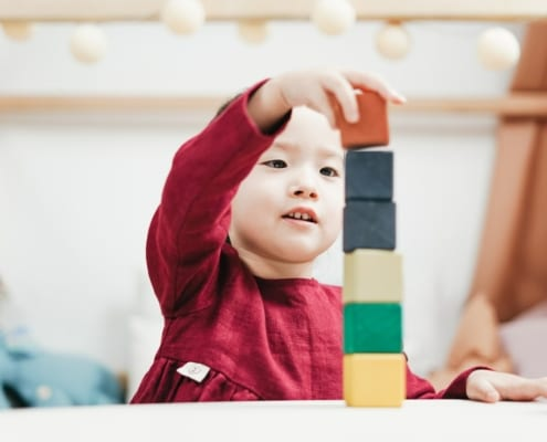 a young girl playing with blocks