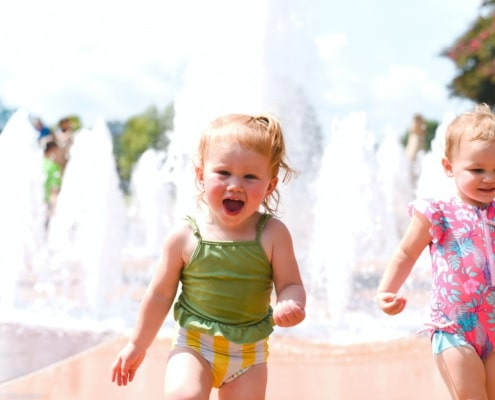 a couple of toddlers playing near a fountain