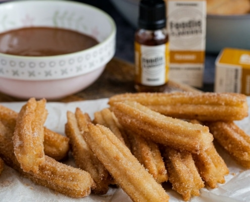 Churros on a paper towel and chocolate sauce on the side